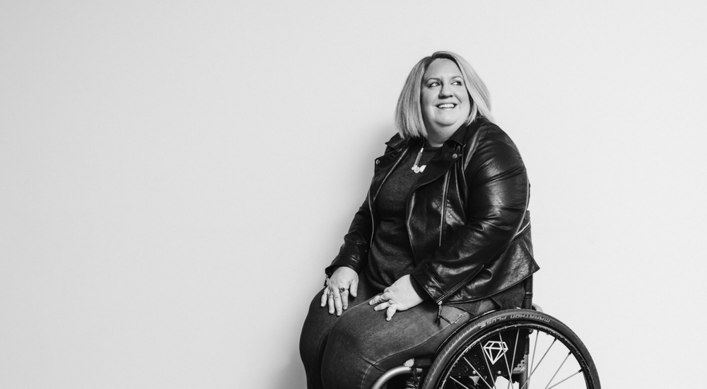Woman in wheelchair looking off camera and smiling