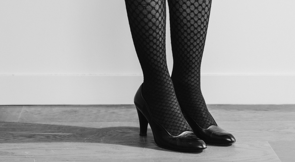A woman's legs wearing patterned stockings and high heels.