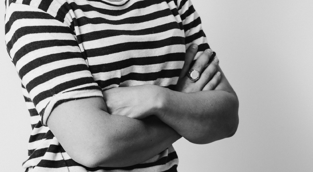 cropped image of a woman wearing a stripey t-shirt with crossed arms.