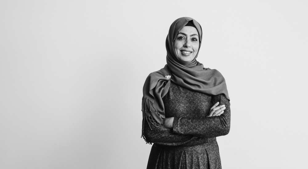 Woman in a hijab with crossed arms smiling at the camera.